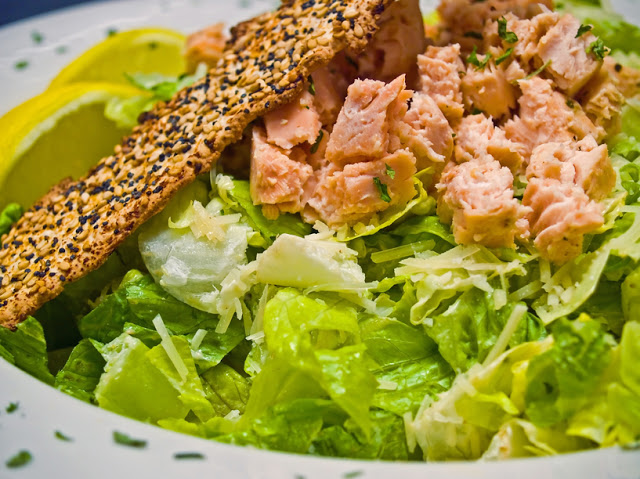 Grilled Salmon Caesar Salad Garnished with a Seeded Cracker