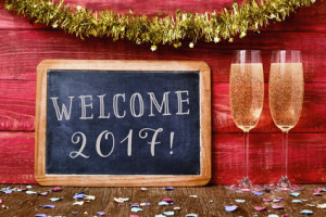 a chalkboard with the text welcome 2017 written in it, some confetti and a pair of glasses with champagne on a red rustic wooden background ornamented with tinsel